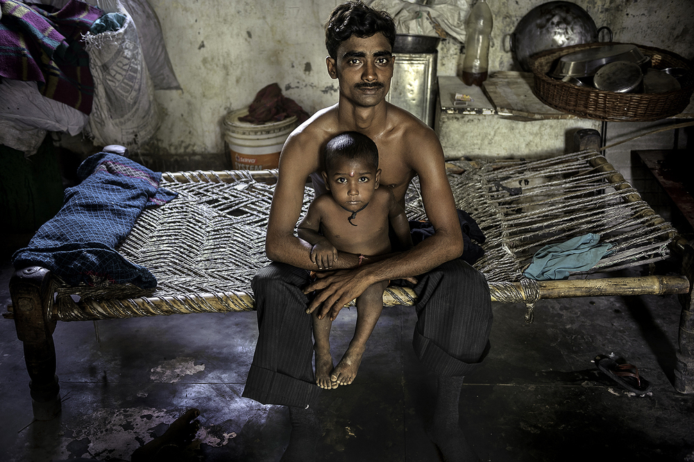Kailesh Chand, 26,  who sits with his son Om Prakash 2, is a machine operator in New Delhi, India.  It is a job his brother had before he lost his leg in a work-related accident. They are squatters in Kale Khan along the Yamuna River in East Delhi living on government property but could be kicked out and have no place to live. He works six days a week and his shift changes daily to make $2 a day. He says his salary is okay now but worries about how he will afford to send his children to school later.  His wife Sunita Devi stays home to watch their infant son Hemant. ©  Renée C. Byer