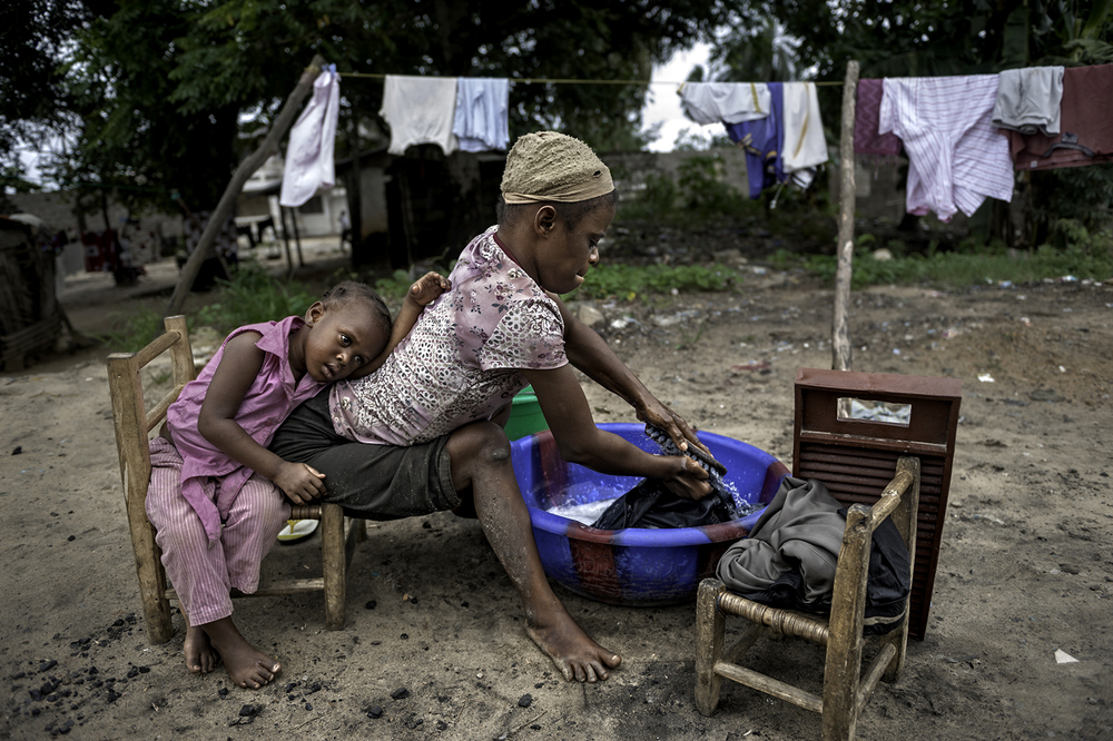 Jestina Koko, 25, with her daughter Satta Quaye, 5. Crippled since the age of three, she depends on her arms to lift and drag herself. She survives by doing laundry for others, selling cookies on the street, and begging in Monrovia, Liberia. ©  Renée C. Byer