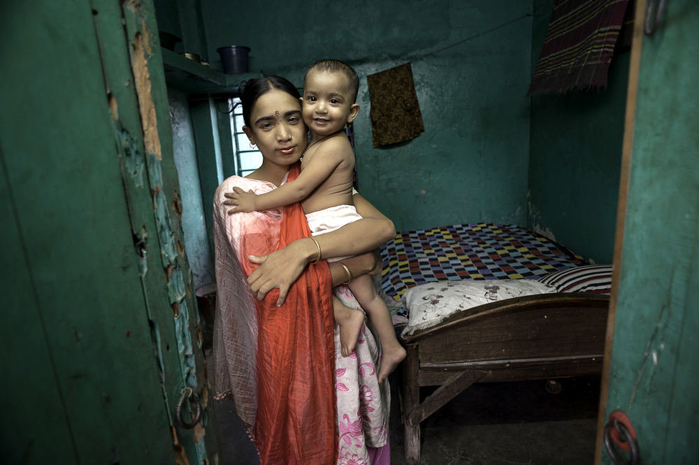 In a brothel in Bangladesh, Labone, 27, takes a moment to hold her young daughter Nupur, 1, who was fathered by a client, before she has to return to her evening's work. ©  Renée C. Byer
