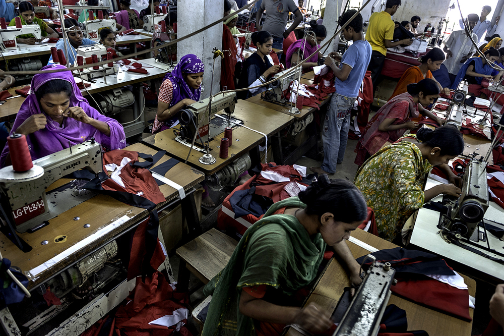 Mumtaz Hassanullah, 32 (far left, in purple), cuts thread with her teeth as she sews continuously in one of Bangladesh's many garment factories. It is a job she does from 8 A.M. to 8 P.M. nearly every day. These are long hours in an often hot environment which on average only pays her about 14 cents an hour, but it is work she accepts for it offers her at least a steady income, an income that she hopes to use to better the lives of her children. It is what is most important to her.©  Renée C. Byer