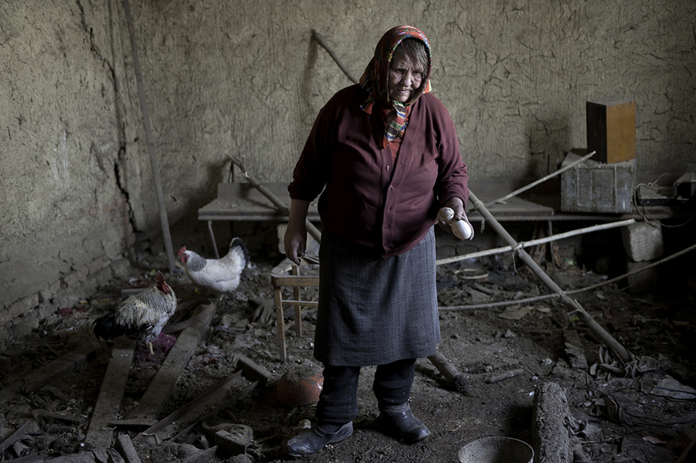 In her home in Moldova, Viorica Bujor, 78, holds two goose eggs that will make up a significant part of her grandchildren's dinner. For twelve years this family has lived in a house with no electricity, broken windows, and no heat. ©  Renée C. Byer