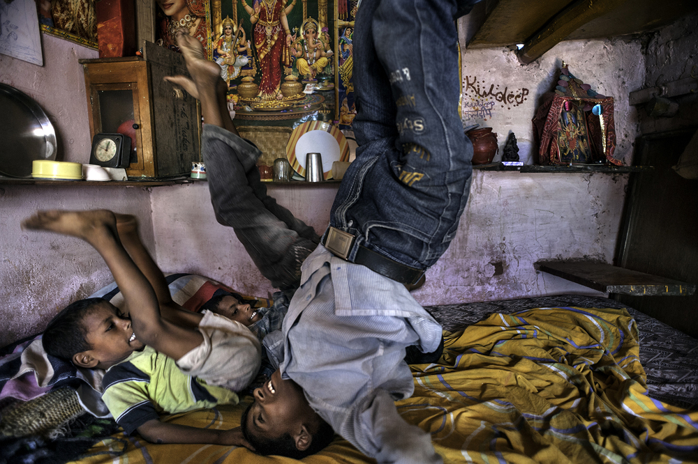 Three of five boys from the family of Dona Devi, 35, and her husband Kamal Singh, 50, play on a bed that occupies their entire living space in the Kusum Pahari slum in South Delhi, India. From left are Ajit Kumar, 5, Dilip Kumar, 9, background and Kuldeep Kumar, 10, foreground. Kusum Pahari slum in south Delhi (opposite Hotel Inter continental) is located on a garbage dump where meat butchers also graze their pigs. The pigs freely roam the neighborhood. There has been a government order to abolish the slum but the people that have been living there for almost 25 years have no where to go. ©  Renée C. Byer