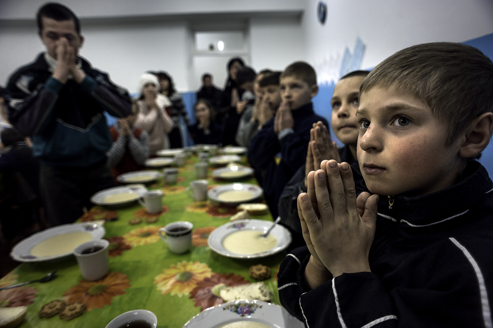 Petru Stepaniuc, 9, right, prays with other children at the Center for Children in Chisinau, Moldova, before a lunch consisting of corn porridge. Petru has lived here since 2009. His father works in Russia but has not sent any money home to help him and his mother, who suffers from alcoholism. This center serves as an orphanage for many children who are left behind when their parents leave the country to try to find work but never return. ©  Renée C. Byer