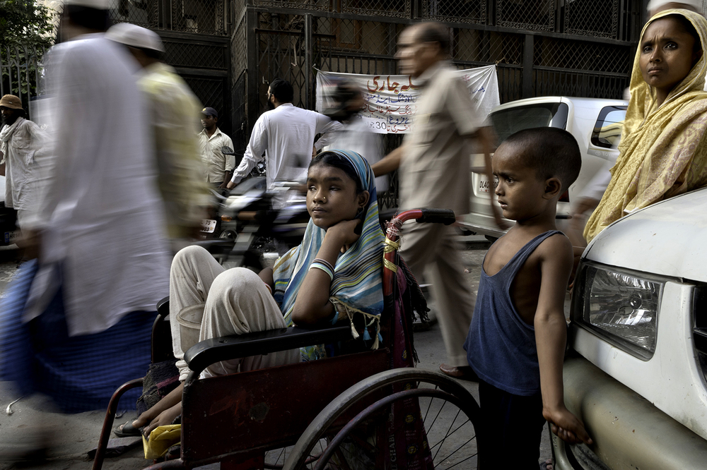 A sea of people walk by Hunupa Begum, 13, who has been blind for the past 10 years and lives close to the Nizamudin Bangala Masjid (Mosque) in New Delhi, India. © Renée C. Byer