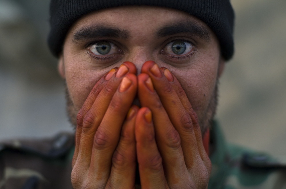 An Afghan National Army (ANA) soldier seen warming his henna stained hands from EID worship on the front lines in Zhari District, Afghanistan. December 18, 2007.  ©Louie Palu/ZUMAPRESS.com