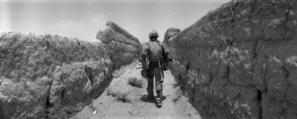 A Canadian soldier walks between narrow mud walls. The path is known as 'Route Nightmare' in Panjwaii District, Kandahar, Afghanistan. The mud walls, unpaved paths and roads are due to lack of development and reconstruction in almost all of the impoverished rural areas allow for planting of land mines and road side bombs by insurgents. Dec. 9, 2010  ©Louie Palu/The Alexia Foundation/ZUMAPRESS.com