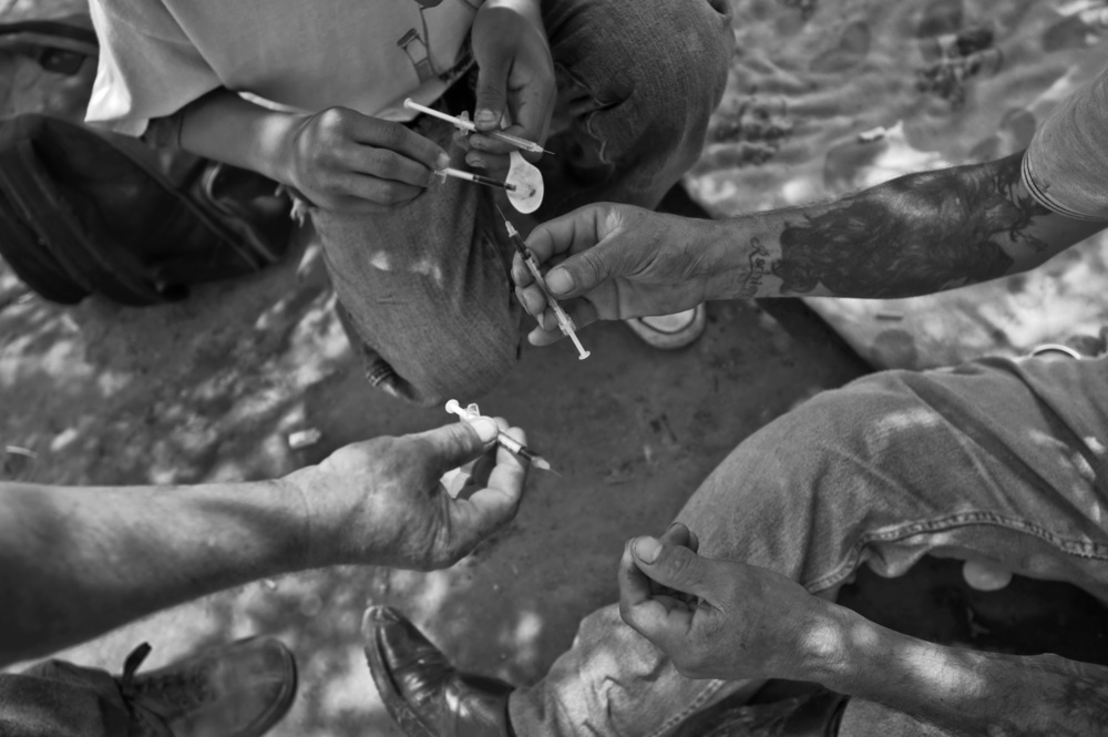 Mexican heroin addicts prepare needles along the Tijuana River in Mexico.  ©Louie Palu/ZUMAPRESS.com