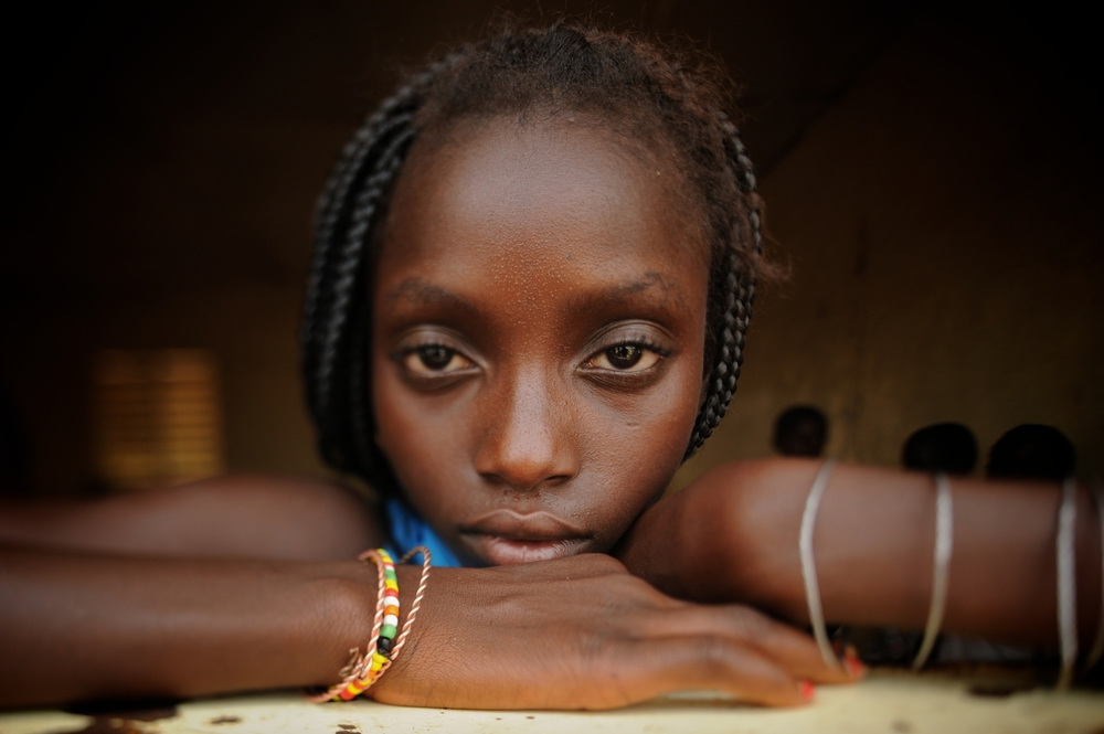 Jenabu Balde  rests her head inside the school in the remote village of Dembel Jumpora in Guinea Bissua. This was one of two images misappropriated for the  #bringbackourgirls  campaign. 2011   ©  Ami Vitale