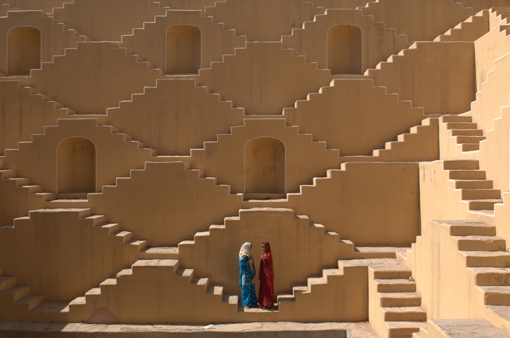 Jasmin  (wearing red) and  Manisha Singh  (white and blue sari) pose at the Baoli at Amer, a water well in the city of Japiur in India's Rajasthan Thar desert. 2009  © Ami Vitale