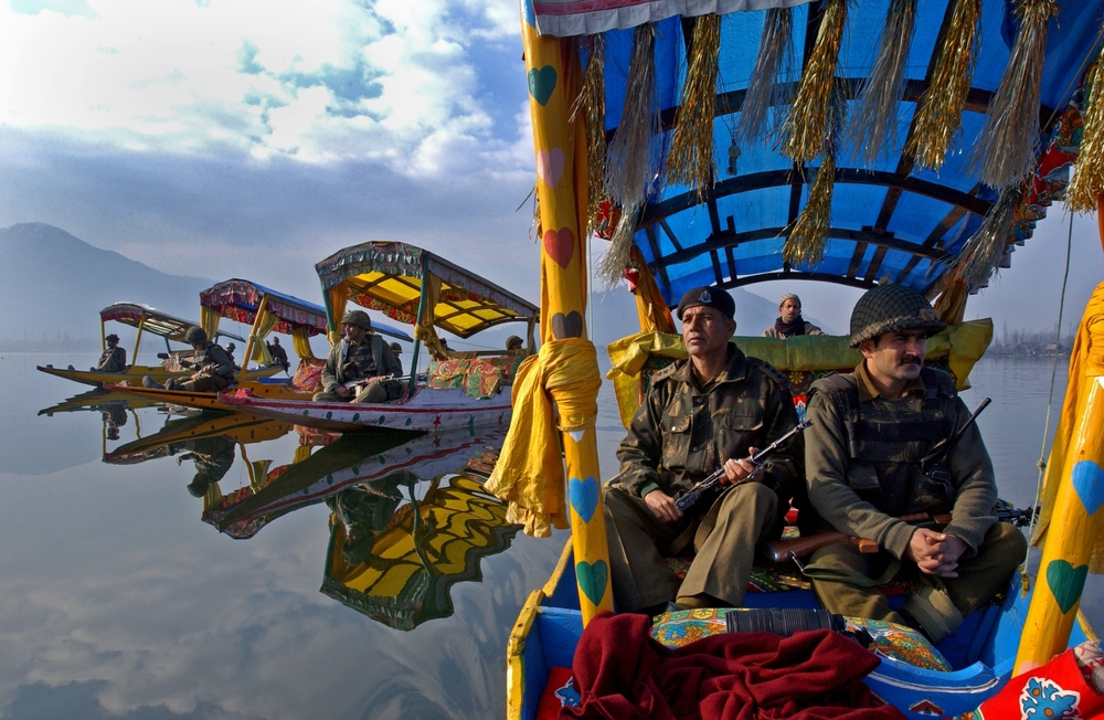 Indian Border Security Force Officers patrol the picturesque Dal Lake in the summer capital of  Srinagar in the Indian held state of Kashmir.  Once a tourist hotspot, the only  visitors to this magnificent landscape these days are Indian soldiers. 2002  © Ami Vitale