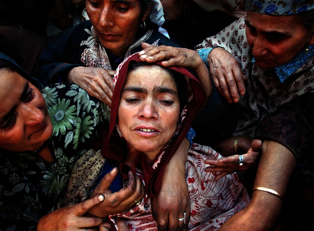 Relatives of Naz Banu, who was killed during an attack on leading politician Sakina Yatoo, mourn over her body during her funeral in the northern Kashmir town of Mirhama. 2002   © Ami Vitale