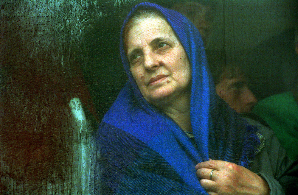 An ethnic Albanian refugee from Kosovo sits in a bus waiting to be transported to the Brazda camp near Skopje, Macedonia. 1999  © Ami Vitale