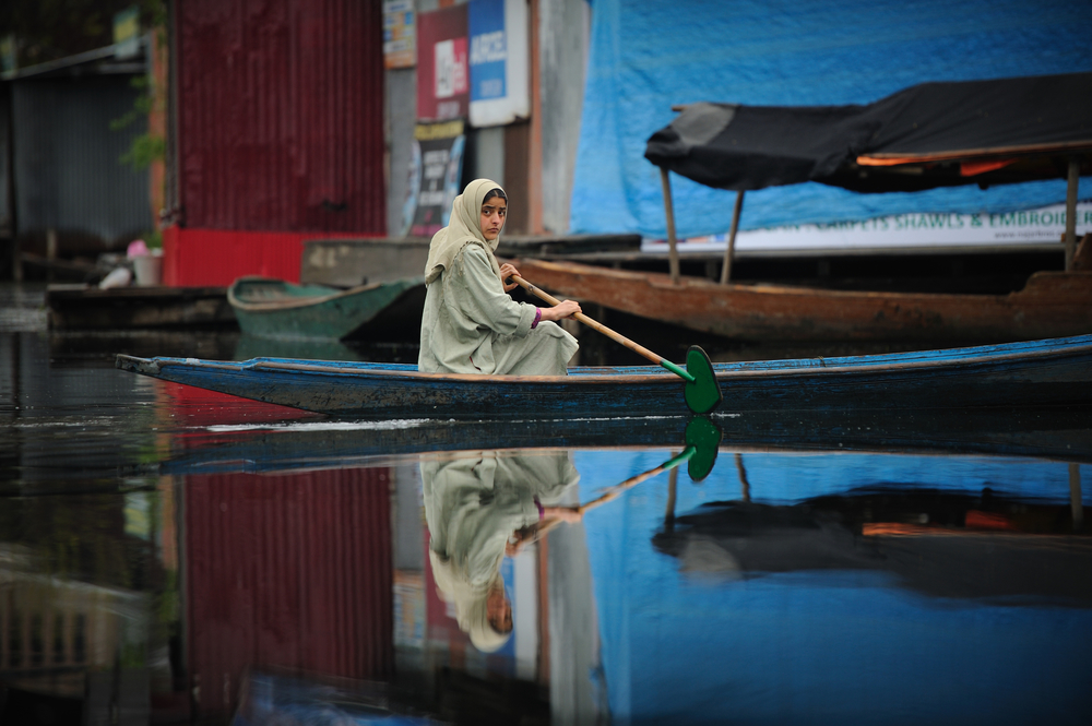 A Kashmiri girl paddles to the market before school in the early hours  on Dal Lake in the troubled summer capital of Kashmir, Srinagar India. 2012   © Ami Vitale