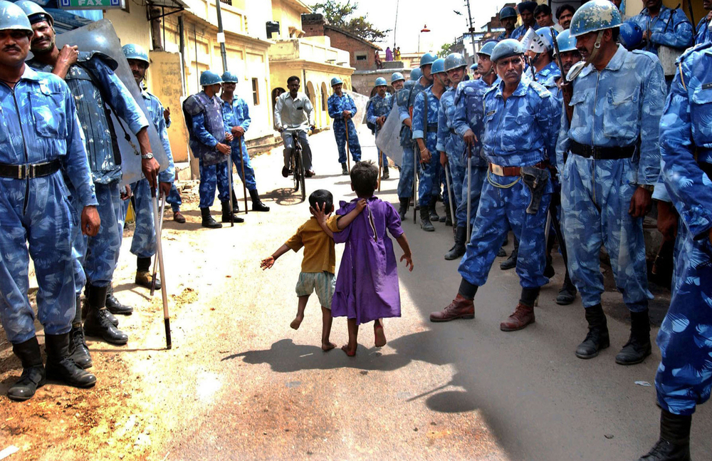 Children run through the streets as the Indian Rapid Action Force conduct a search in the disputed northern Indian city of Ayodhya. 2002   © Ami Vitale