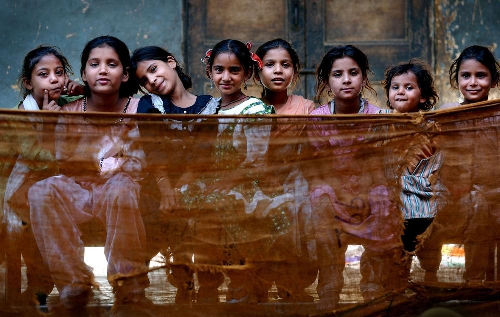 Muslim children sit inside Dariya Khan Ghhumnat Rahat refugee camp set up outside a school in the state of Gujarat in Ahmedabad, India. 2002 © Ami Vitale