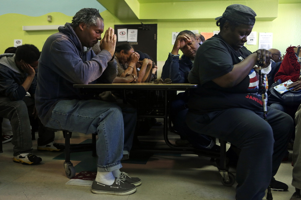 (left to right) Phillip House, Richard Lofton and Beverly Fails pray before receiving dinner at Mother Brown's Kitchen next to a proposed shelter at 2115 Jennings Street in in the Bayview district of San Francisco. © Scott Strazzante/San Francisco Chronicle