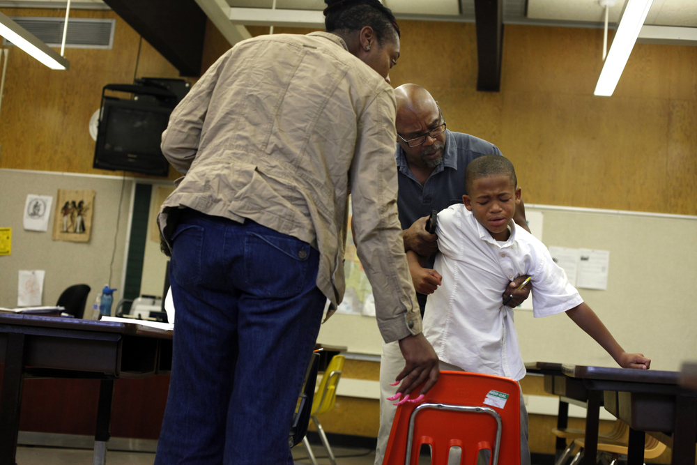 Crystal Watson-Johnson, Assistant to the Dean, and Dean Spencer Hooper try to console fourth-grader Delyon Rice after he was sent to the restoration room for punching his teacher. Students are sent to the restoration room for screaming, hitting teachers, fighting, or generally acting out. © Lacy Atkins/San Francisco Chronicle