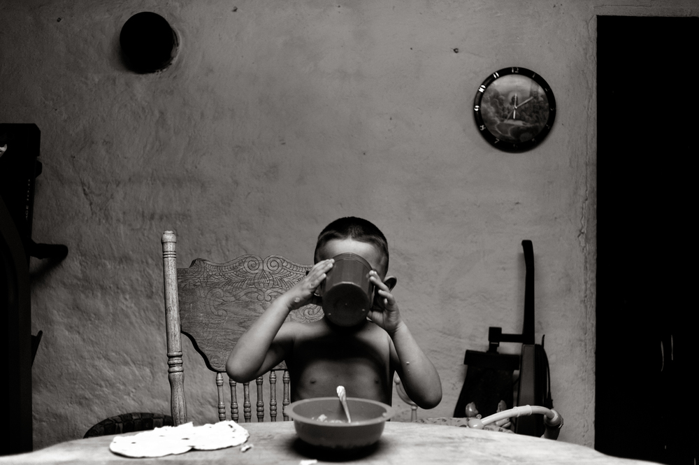 Jozif Martinez, 4, drinks a cup of Kool Aid at the dinner table in the family home in Capulin, CO.  He ate tortillas and bacon for dinner.  ©Judy DeHaas/The Denver Post