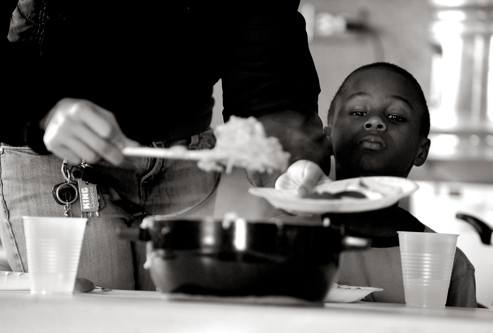 Shawnwunza Smith, 8, watches Analisa Angel serve macaroni and cheese to the children enrolled in the day-care program at Sun Valley Youth Center. The center offers tutoring, mentoring, meals and recreation to neighborhood children who have few alternatives. © Craig F. Walker/The Denver Post