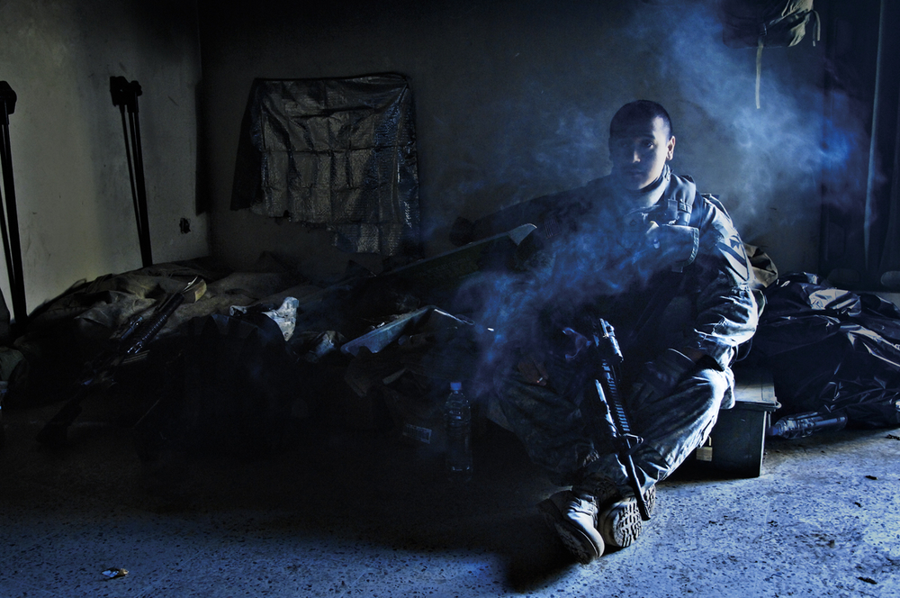 Before going on patrol, a U.S. Army soldier smokes a cigarette on his cot at a remote combat outpost in Buhriz, Iraq. 2007 © Stacy L. Pearsall