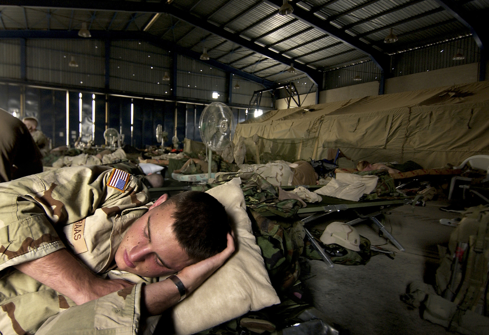 After standing guard during the night, a soldier tries to sleep at an abandoned car dealership in Baghdad, Iraq. 2003 © Stacy L. Pearsall