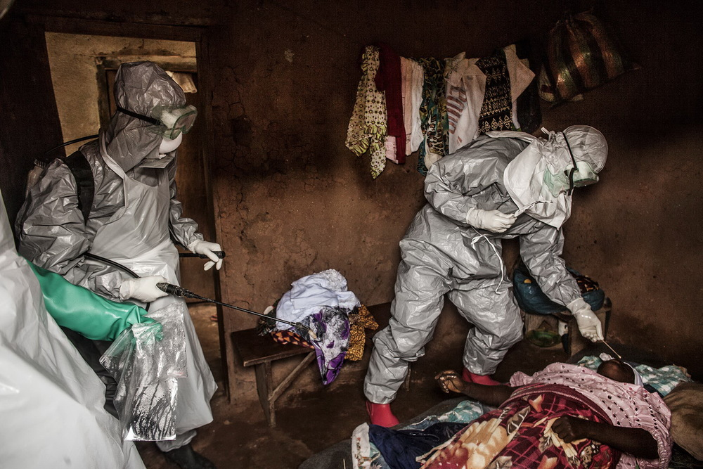 Members of a Red Cross burial team take samples from a  woman suspected of dying of Ebola in the village of Dia, Sierra Leone. August 18, 2014 © Pete Muller/Prime for the Washington Post