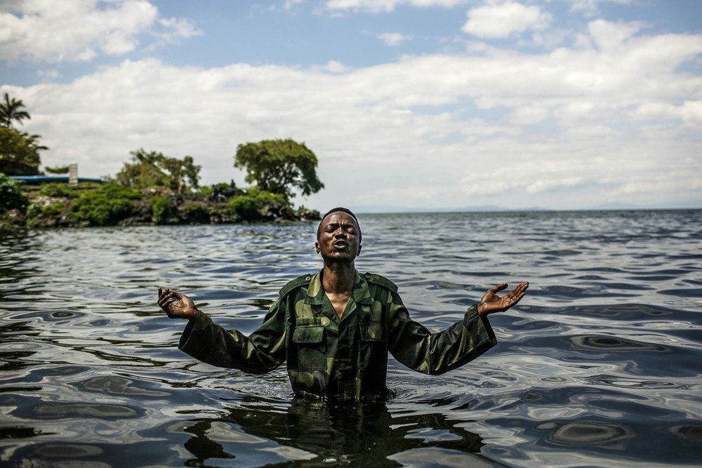 Congolese military chaplain Col. Aaron Kubuta prays in Lake Kivu after baptizing a group of soldiers. 2013 Democratic Republic of Congo © Pete Muller for the New York Times