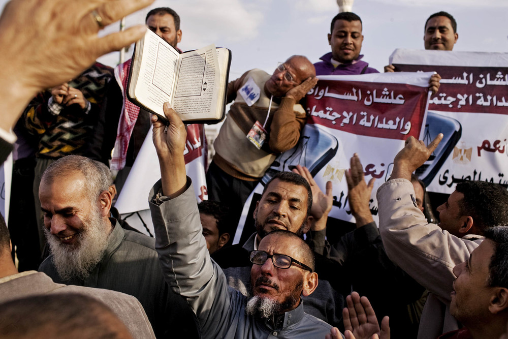 A supporter of Egyptian President Mohamed Morsi holds up a copy of the Koran during a rally in Cairo, Egypt on Tuesday, December 11, 2012. Pro-government supporters turned out by the thousands to express their support for the Islamist President and a controversial draft constitution that is scheduled to go to referendum on Saturday, December 15th. Many groups opposed to President Morsi claim that the draft constitution undermines numerous political freedoms and human rights. Egypt 2012 © Pete Muller for the Washington Post