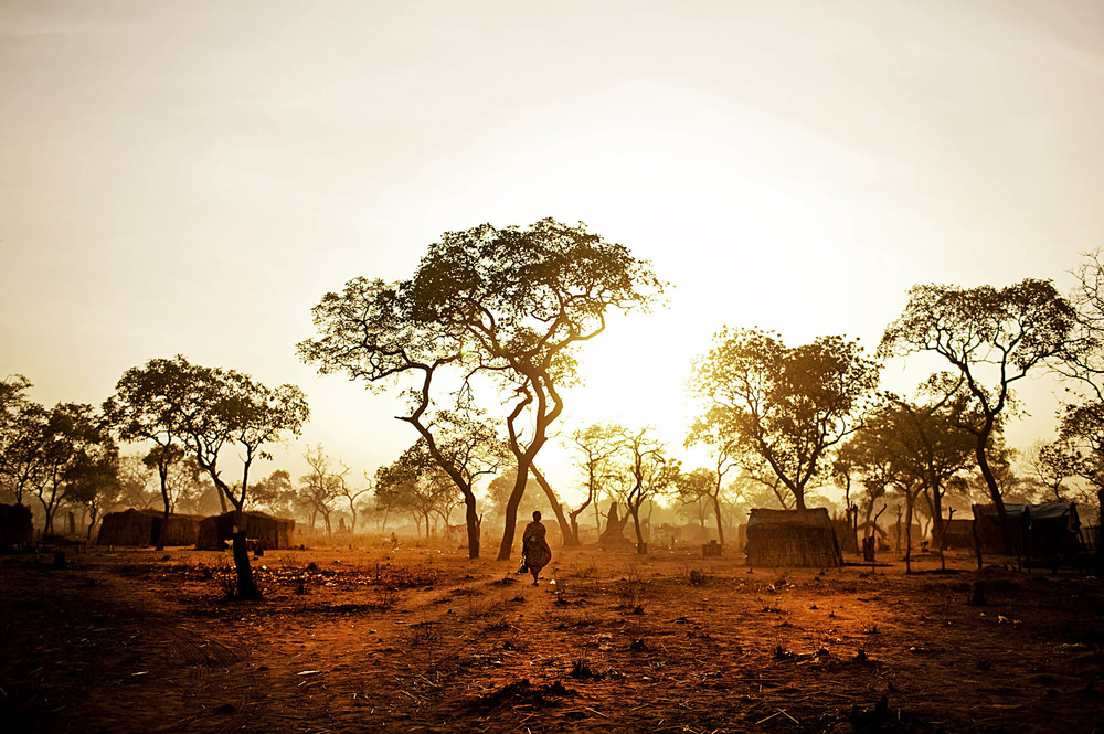 A Nuba refugee from South Kordofan navigates the Yida refugee camp at dawn. In the wake of independence, southern-aligned rebels in the South Kordofan and Blue Nile border states were cut off from their historic allies and remained under the enduringly harsh rule of Khartoum. Feeling isolated and vulnerable, fighters commenced a new rebellion aimed to gain autonomy for their regions. The renewed battle has caused more than 100,000 people to flee their homes. Sudan 2012 © Pete Muller