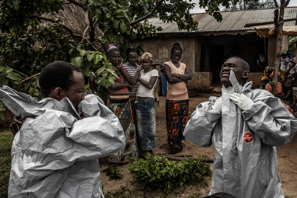 "Members of a Red Cross burial team put on personal protective equipment before entering the home of a woman suspected of dying of Ebola in the village of Dia on Monday, August 18, 2014. So-called ""safe burials,"" conducted by the International Federation of the Red Cross, are conducted in accordance with rigorous safety procedures. The dead bodies of Ebola victims are extremely infectious. © Pete Muller/Prime for the Washington Post"