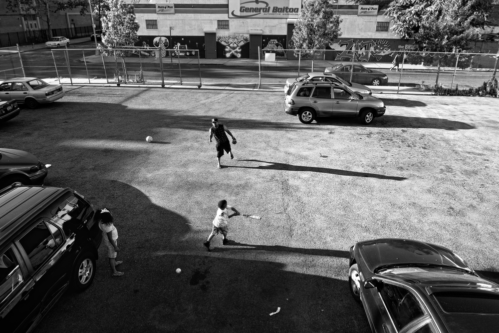 A father uses a parking lot to practice baseball with his son and daughter in the Bronx. 2012 © Zun Lee