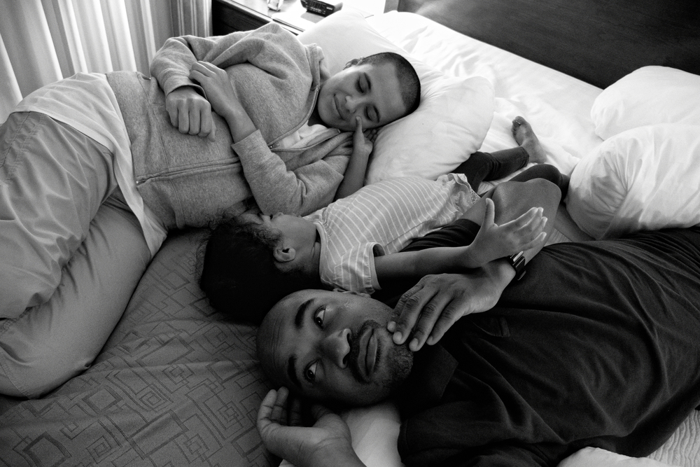 The Richardsons relax in their hotel room after a taxing visit to Carlos' father in Augusta, GA. 2012 © Zun Lee