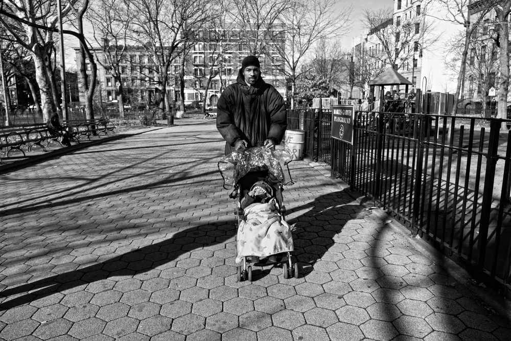 Guy Miller with son Guy Jr. on a chilly day at Marcus Garvey Park. 2012 © Zun Lee