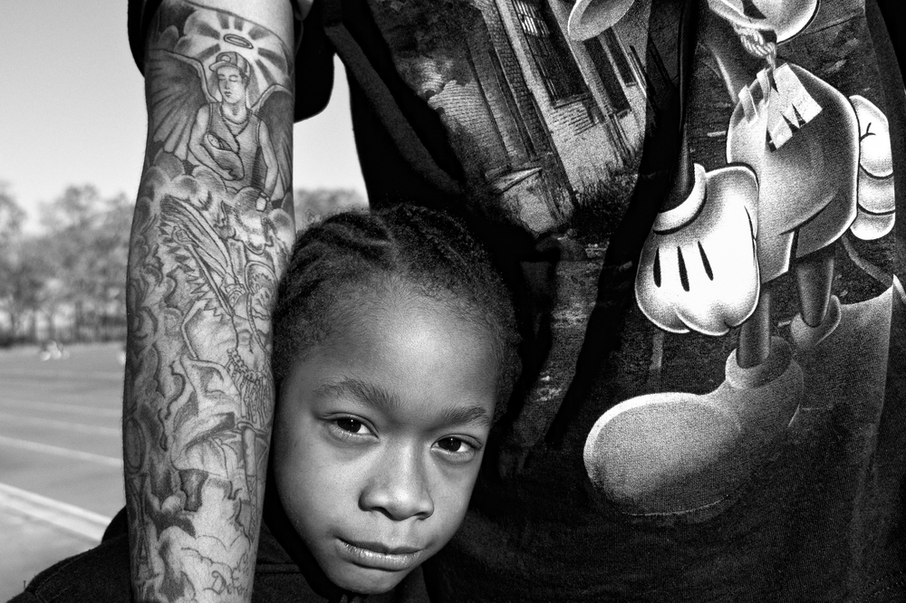 "Jerell Willis holds his son Fidel. Jerell's right arm has a tattoo depicting him as Fidel's guardian angel. ""I got the tattoo when I won custody of Fidel,"" says Jerell. ""The tattoo is a reminder of my duty to protect him."" New York, NY, USA. November 2011. © Zun Lee"