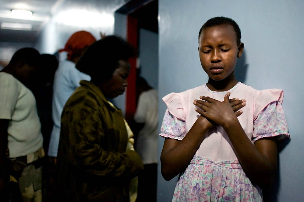 Salula, Escaped from Marriage:   Narok, Kenya. Salula Sylvia Naingisa, 11, prays during an evening fellowship inside the girl's dorm at the Tasaru Safehouse for Girls. © Marvi Lacar