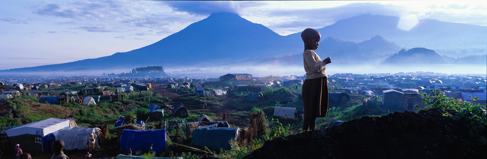 A panorama of a refugee girl standing on a hill with her Rwanda camp city and mountains in the background LIFE 1997 © Joe McNally