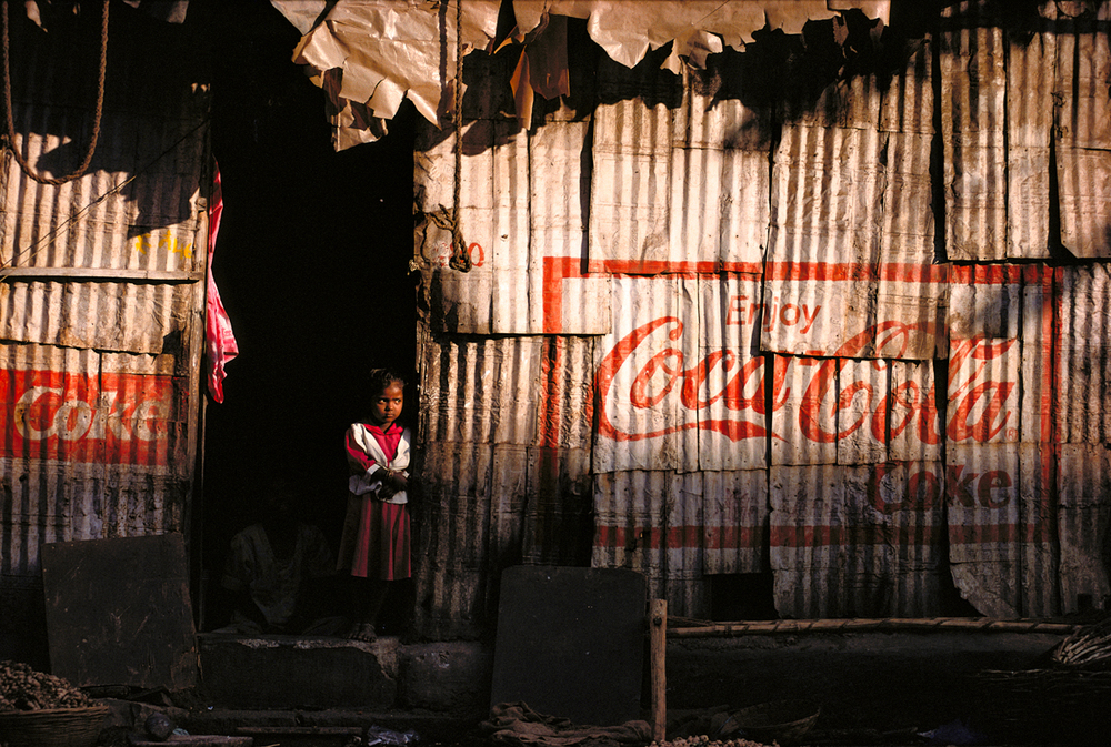 An Indian girl stands in the doorway of her Mumbai slum 1999 © Joe McNally