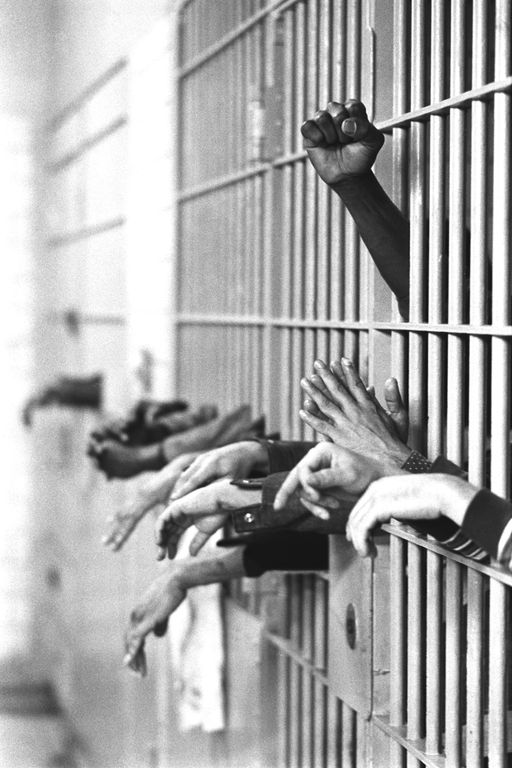 Hands from behind the bars at Tombs Prison, built in 1840 with granite from the old Bridewell Prison in City Hall. September 28, 1972.  © Jean-Pierre Laffont
