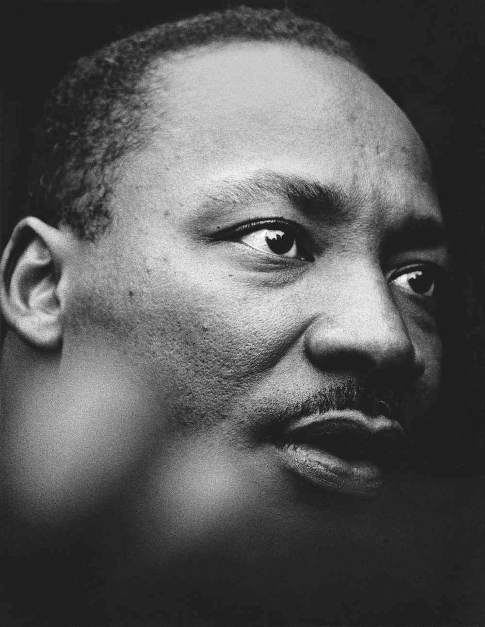 Martin Luther King Jr. outside the UN building delivering a speech denouncing the Vietnam War. We can see the UN building reflected in his eyes.  April 15, 1967  © Jean-Pierre Laffont
