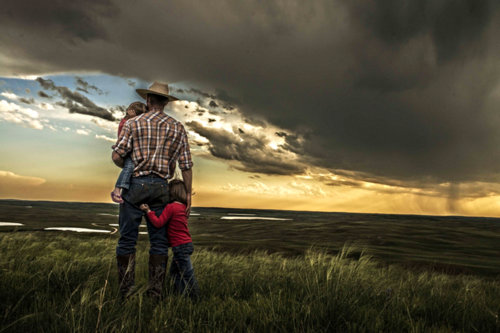 Tyler Messersmith with his two oldest daughters June, left, and Ava, right, overlooking their ranch outside Lakeside, Nebraska. © Bill Frakes/Straw Hat Visuals