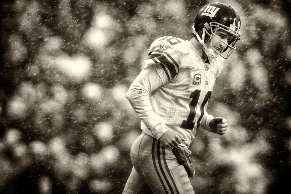 Giants QB Eli Manning runs through the driving rain and sleet during New York's 38-21 defeat of the The Buffalo Bills at Ralph Wilson Stadium in Orchard Park, NY. December 23, 2007 © David Bergman