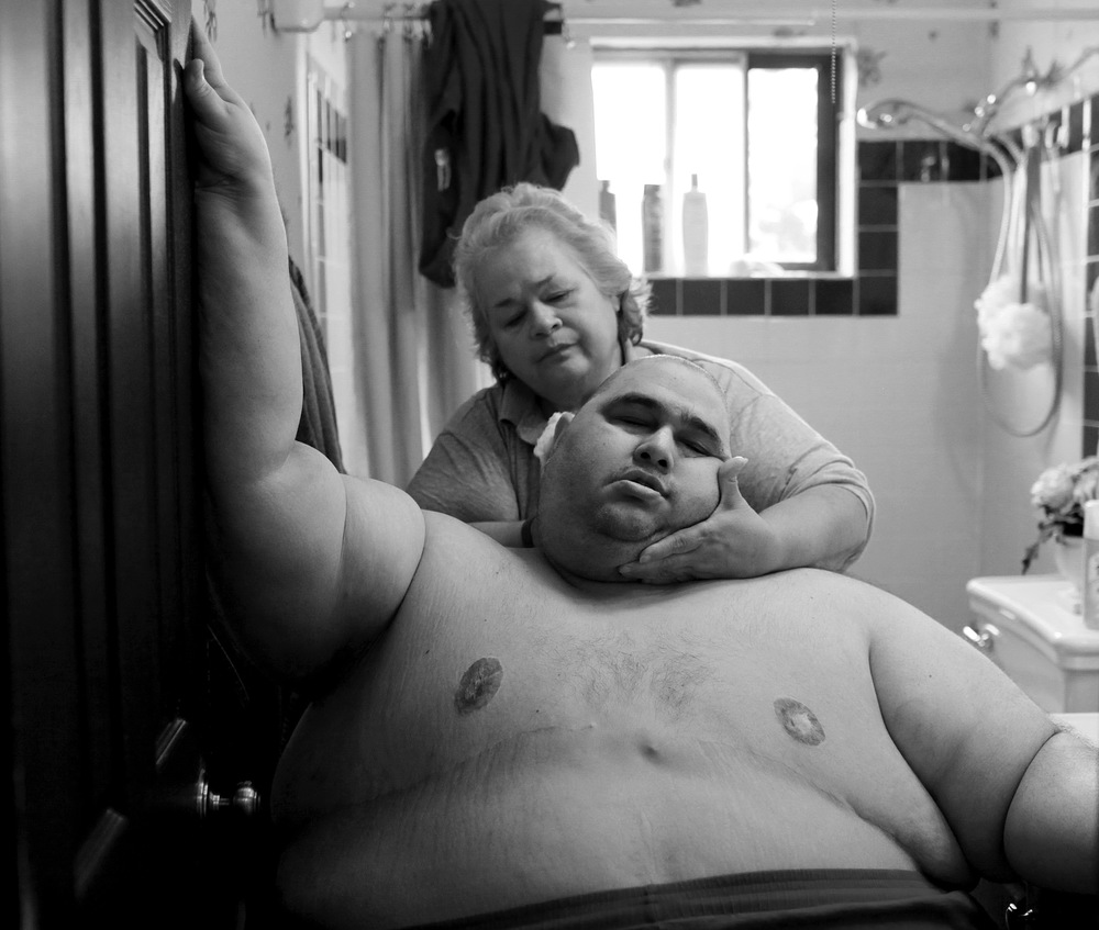 At almost 600 pounds, Hector Garcia Jr. finds simple daily tasks like bathing a challenge. He struggled to walk across the hall from his bedroom to the bathroom so that his mother, Elena Garcia, could wash him after cutting his hair. © Lisa Krantz/San Antonio Express-News/ZUMA Press