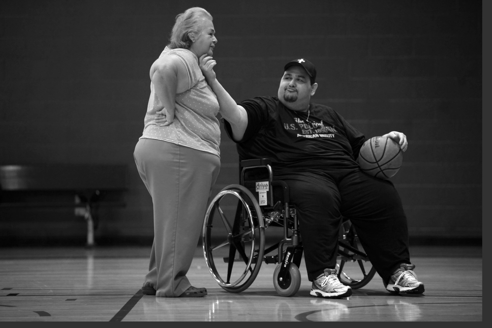 Hector Garcia Jr. teases his mother and caretaker, Elena Garcia, as he shoots baskets at the West-side Family YMCA. When Garcia began going to the YMCA, he was only able to walk in the pool. As he lost weight and became more mobile, he could eventually lift weights.  © Lisa Krantz/San Antonio Express-News/ZUMA Press