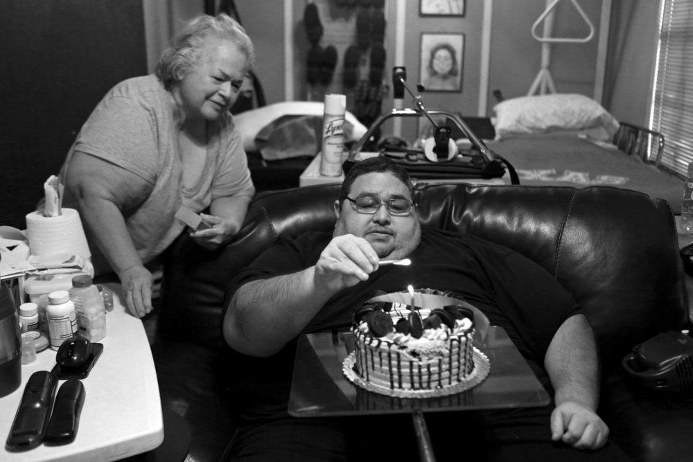 Hector Garcia Jr. lights the candle on his cake for his 49th birthday as his mother, Elena Garcia, begins to sing to him at their home.  © Lisa Krantz/San Antonio Express-News/ZUMA Press