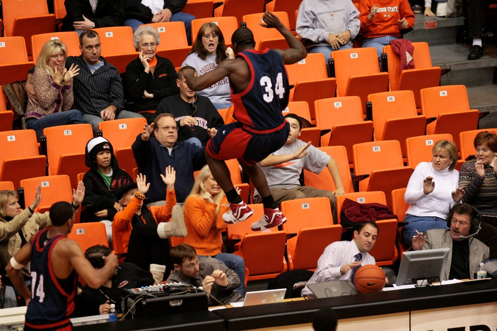 A player from Fresno State leaps into the stands while chasing after a loose ball. © Sol Neelman/The Oregonian
