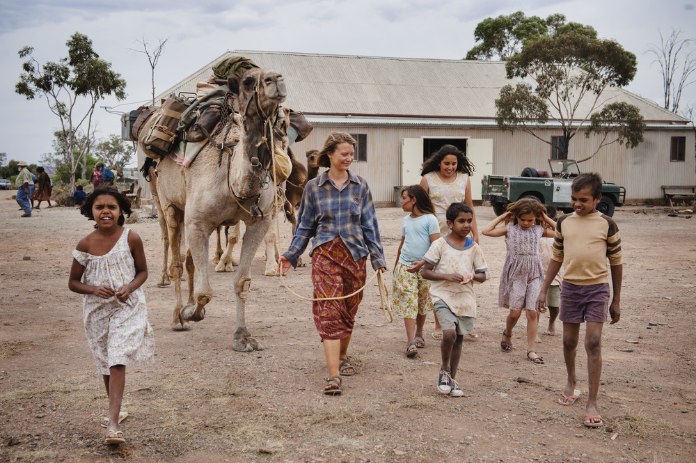 Robyn (Mia Wasikowska) and her camels enter the Docker River Community, echoing Rick's photo of the real Davidson surrounded by aboriginal children as she entered the real Docker River.   ©  Matt Nettheim/See-Saw Films