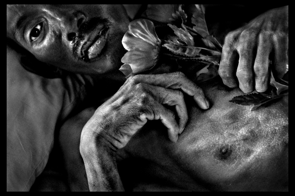 Saong (38) lies in an Aids hospice in Thailand, holding a plastic flower. World Press Photo Contest 1999, People in the News, second prize singles. © Nancy Andrews/The Washington Post