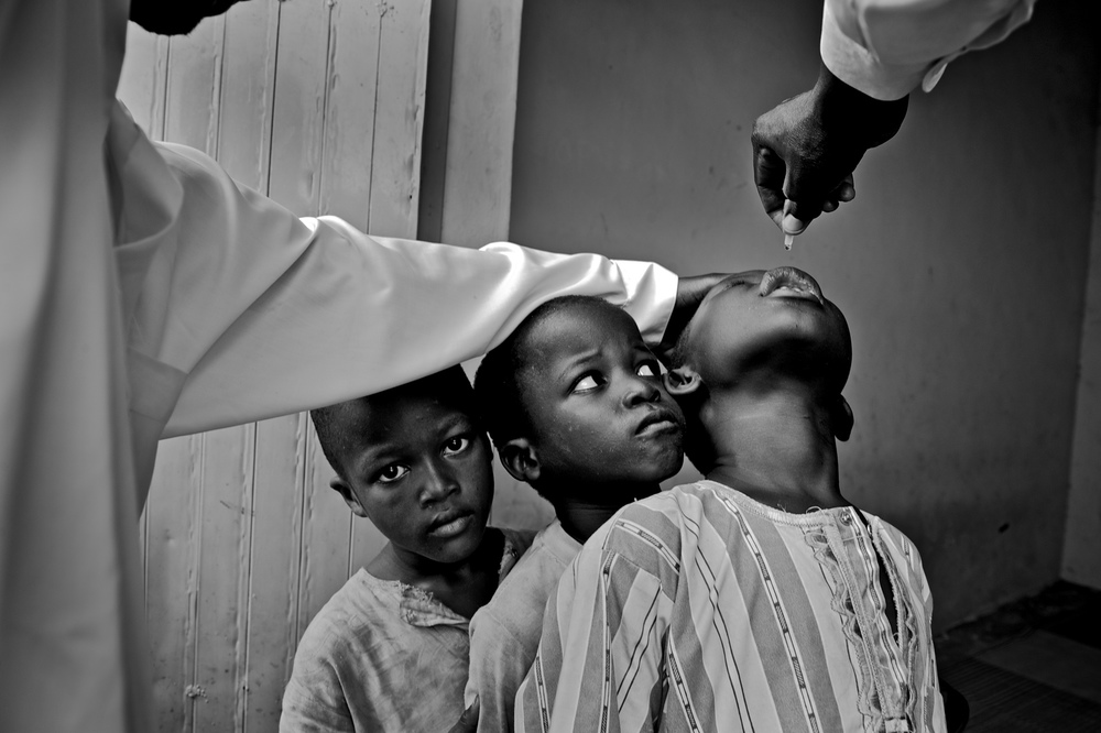 Nigeria's Polio Nightmare: Kano, Nigeria - Boys wait their turn for vaccinator Sani Mohammed to administer two drops of polio vaccine on their tongues at a stationary vaccine site. © Mary F. Calvert/The Washington Times/ ZUMAPRESS.com