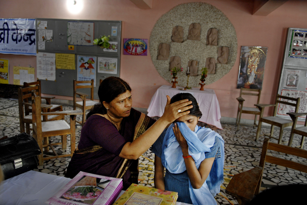 Lost Daughters: Sex Selection in India: Neelam Chaturvedi, left, co-founder of the women's advocacy group Sakhi Kendra in Kanpur, India, comforts Aradhana Rawat, 17, who lives at the Sakhi Kendra home in Kanpur. Sahki Kendra is sheltering the doe-eyed young woman, whose father would tie her to a bed and sexually abuse her. At one point, he tried to slit her throat with a machete.  © Mary F. Calvert/ ZUMAPRESS.com