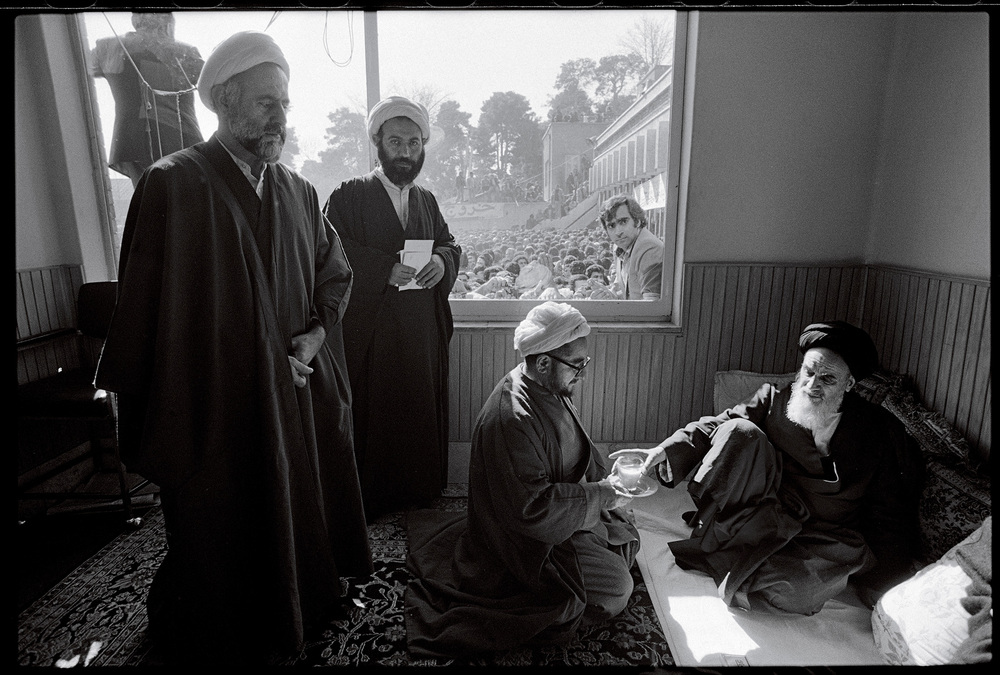 "Ayatollah Khomeini is served tea in his room at the Refah School by Sadegh Khalkhali, who later became known as ""the hanging judge."" Tehran, February 5, 1979. © 2015 David Burnett/Contact Press Images"